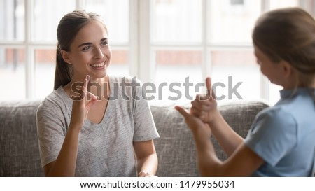 Teacher and schoolkid show symbols with hands sit on couch, young mother talk with deaf daughter use visual-manual gestures focus on mom. Little girl during sign language learning lesson concept image #1479955034