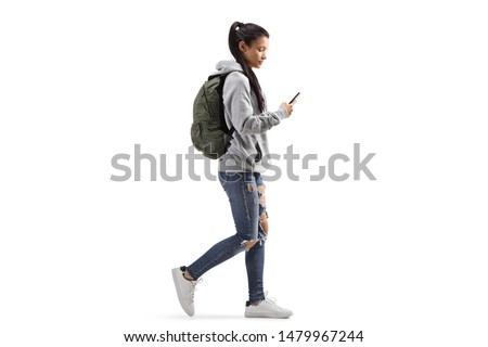 Full length profile shot of a female student with a backpack walking and looking into a mobile phone isolated on white background #1479967244