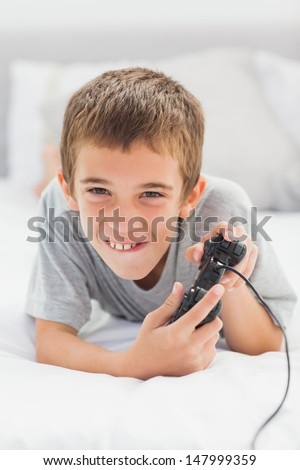 Concentrated little boy lying on bed playing video games at home #147999359