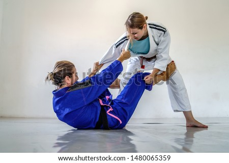 De la riva guard in brazilian jiu jitsu bjj training sparring two female women athletes fighters drilling techniques for the competition advanced guard black and brown belt #1480065359