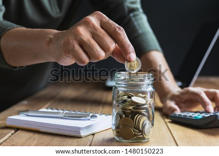 Men are Saint documents about save money and put coin in glass jar on desk on black background. #1480150223