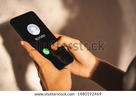 Woman Block a Phone Number or incoming Call from a anonymous stalker or Ex boyfriend. Stalking or bullying with phone concept. Stalker caller, scammer or stranger. Woman blocking incoming call. #1480192469