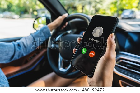 Unknown number calling while car driving. Phone call from stranger. Person holding mobile and smartphone in livingroom late. Unexpected call disturbs at car ride. #1480192472