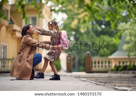 young businessmom hugging her little gilr after school #1480193570
