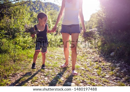 Mother and son picking flowers / herbs in nature. #1480197488