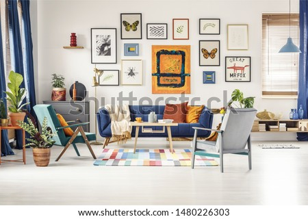 Simple posters gallery hanging on the wall in bright living room interior with blue sofa, two armchairs, fresh plants and wooden coffee table standing on colorful carpet Royalty-Free Stock Photo #1480226303