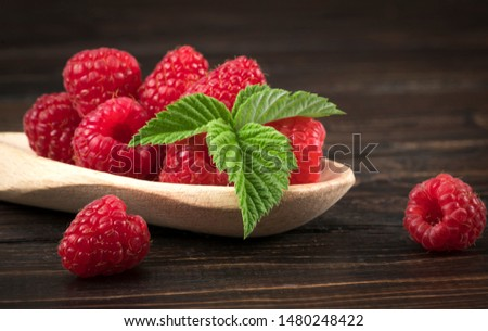 Fresh raspberry in wooden spoon / Close up red raspberries fruit and green leaf on wood background. Fresh raspberry in wooden spoon Close up red raspberries #1480248422