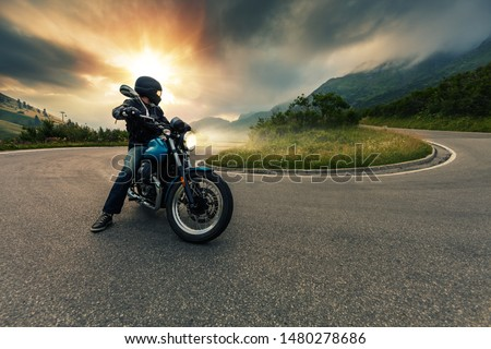 Motorcycle driver posing in Alpine landscape. Lifestyle photo with motion blur effect. #1480278686