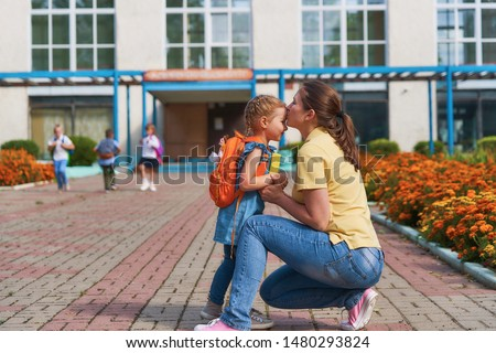 mother accompanies the child to school. mom supports and motivates the student.caring mother gently kisses her daughter on the forehead. positive little girl fun going to primary school.back to school #1480293824