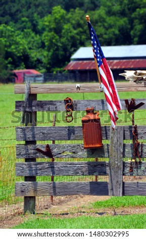 Country gate has eclectic display for American flag.  Fence holds milk can, chain, cow skull and American flag.