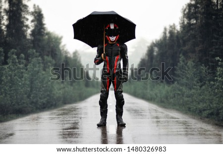 Motorcyclist in full gear and helmet with umbrella in the rain. Motorcyclist in the dark woods. #1480326983