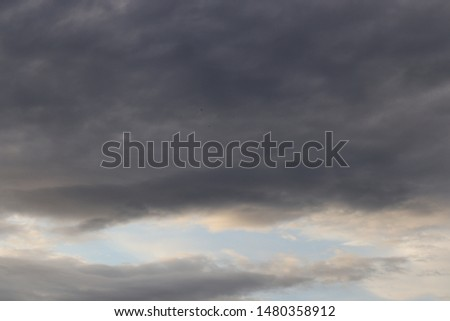 Atmospheric dark grey rain clouds with a small patch of blue sky  #1480358912