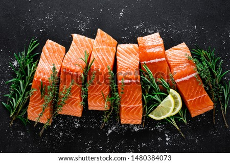 Salmon. Fresh raw salmon fish fillet with cooking ingredients, herbs and lemon on black background, top view #1480384073
