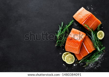 Salmon. Fresh raw salmon fish fillet with cooking ingredients, herbs and lemon on black background, top view #1480384091