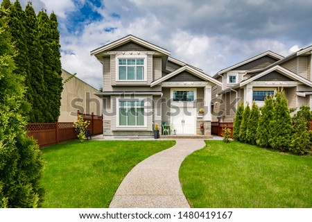 Small family house with curved concrete pathway over green lawn on front yard #1480419167
