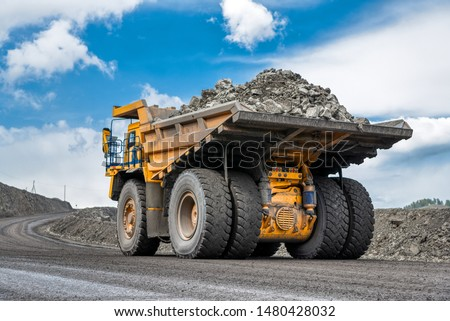 Rock transportation by dump trucks. Large quarry yellow truck. Transport industry. Mining truck is driving along a mountain road. #1480428032
