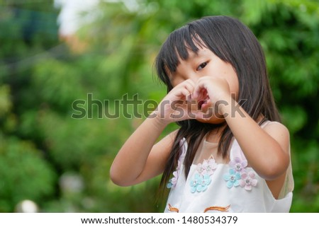 A lovely little Asian girl is playing, making a heart shape hands sign and standing in the garden background. #1480534379