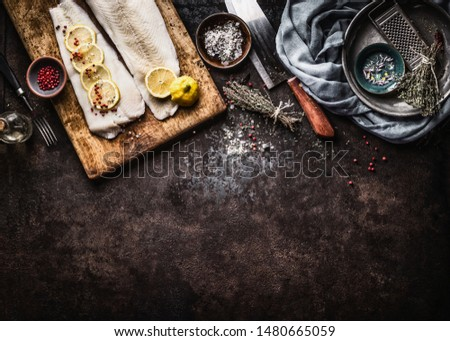 Food background with raw cod fillet with lemon slices and herbs on rustic background with cutting board and knife, top view. Fish cooking preparation. Healthy diet food. Copy space for your design