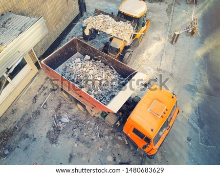 Bulldozer loader uploading waste and debris into dump truck at construction site. building dismantling and construction waste disposal service. Aerial drone industrial background Royalty-Free Stock Photo #1480683629