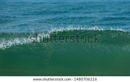Close up of blue, green sea waves isolated in blue background. Morning with clear water outdoor picture of shining foamy ocean high tide current in summer, tropical beach vacation design template.