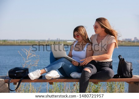 Two young female girlfriends having fun while sitting on a bench while one showing to screen of a laptop while another one is laughing outside. Portrait. #1480721957