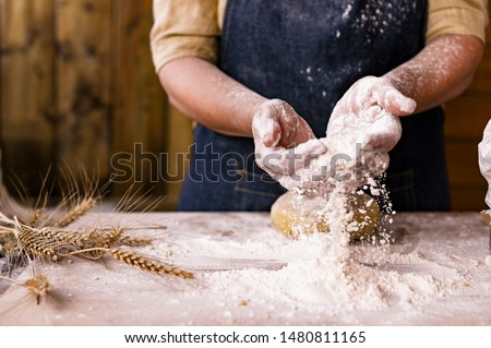 Women's hands, flour and dough. Levitation in a frame of dough and flour. A woman in an apron is preparing dough for home baking. Rustic style photo. Wooden table, wheat ears and flou.Emotional photo #1480811165