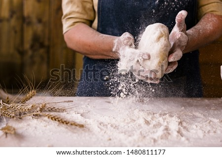 Women's hands, flour and dough. Levitation in a frame of dough and flour. A woman in an apron is preparing dough for home baking. Rustic style photo. Wooden table, wheat ears and flou.Emotional photo #1480811177