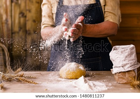 Women's hands, flour and dough. Levitation in a frame of dough and flour. A woman in an apron is preparing dough for home baking. Rustic style photo. Wooden table, wheat ears and flou.Emotional photo #1480811237