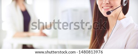 Smiling businesswoman or helpline operator with headset and computer at office #1480813976
