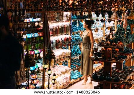 Beautiful girl in a souvenir shop in Morocco. Girl chooses a souvenir Oriental shop. Street shop. Moroccan Souvenirs. Oriental bazaar. Moroccan Bazaar. Tourist shop. Turkish Bazaar #1480823846