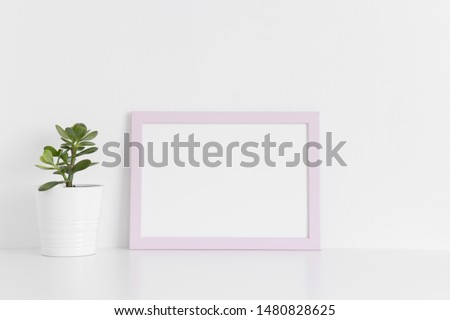 Pink frame mockup with a crassula plant in a pot on a white table.Landscape orientation. #1480828625