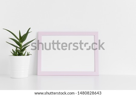 Pink frame mockup with a aloe vera in a pot on a white table.Landscape orientation. #1480828643