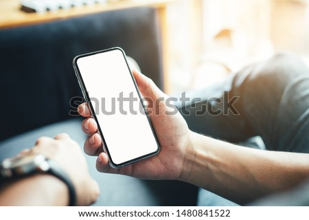 Mockup image blank screen cell phone.men hand holding texting using mobile on sofa at home office.white empty space for advertise text. contact business,people communication,technology device concept Royalty-Free Stock Photo #1480841522