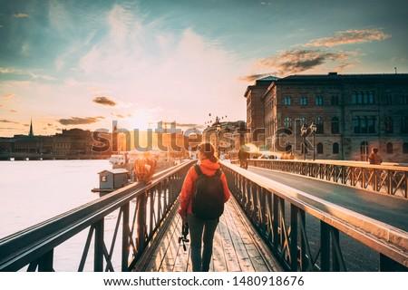 Stockholm, Sweden. Young Caucasian Woman Lady Tourist Traveler Walking On Famous Skeppsholmsbron - Skeppsholm Bridge. Popular Place, Landmark  And Destination In Stockholm, Sweden. #1480918676