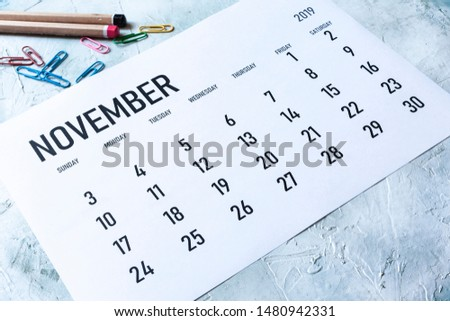 Simple 2019 November monthly calendar on table with office supplies #1480942331