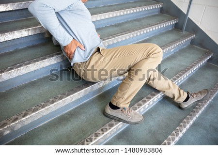 Mature Man Lying On Staircase After Slip And Fall Accident Royalty-Free Stock Photo #1480983806