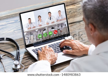 Close-up Of Doctor Having Video Conference On Laptop At Wooden Desk #1480983863