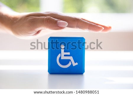 Close-up Of A Person's Hand Protecting Blue Cubic Block With Disabled Icon #1480988051