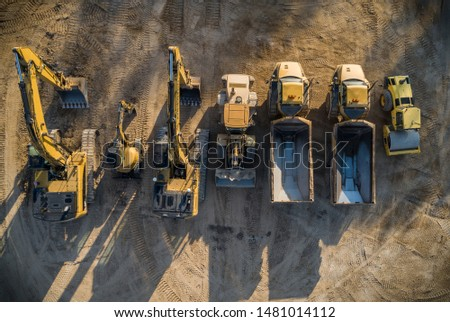 Construction dirt moving equipment lined up for the night. Royalty-Free Stock Photo #1481014112