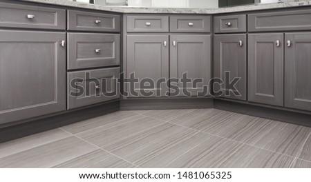 gray shaker style kitchen / vanity / bathroom cabinet with chrome color rectangular handles, porcelain floor tiles #1481065325