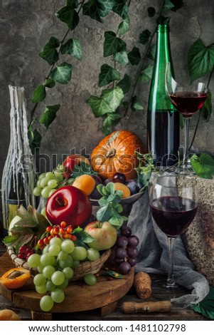 Fruit with red wine. Classic beautiful still life with a glass of red wine and fruit on an old vintage wooden dark table. Concrete background. Dramatic light. Rustic style. Candles in the candlestick