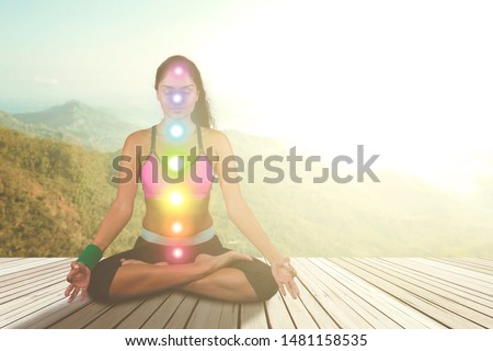 Picture of Indian woman doing meditation with colored chakra points on her body. Shot at nature
