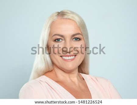 Portrait of mature woman with beautiful face on grey background #1481226524