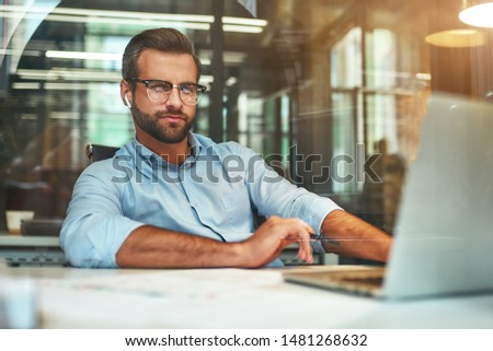 Successful businessman. Young bearded man in eyeglasses and formal wear working with laptop while sitting in the modern office #1481268632
