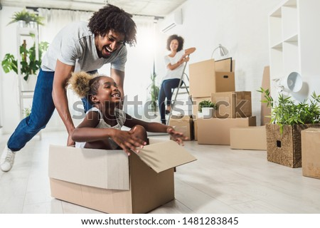 Young Smiling Happy African-american Family Unpacking During Move. New Home. Little preschooler daughter sitting in cardboard box, father rolling her. Smiling mother looking them. #1481283845