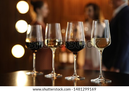Glasses of different wines on table against blurred background #1481299169