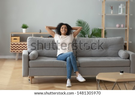Happy african American young woman sit relax on cozy couch hands over head happy to move to new apartment, smiling black millennial girl rest on comfortable sofa in living room dreaming #1481305970