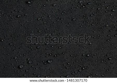 dark gray waterproof hydrophobic flat cloth closeup with rain drops background #1481307170
