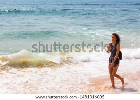 Hikkaduwa, Sri Lanka -  12/18/2017 - Young beautiful white girl walking on the shore of the Hikkaduwa beach in Sri Lanka #1481316005