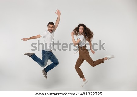 Joyful young man and happy millennial girl jumping high with raised hands and bent in knees legs, flying, having fun during photo shooting process near softbox light, isolated grey background. #1481322725